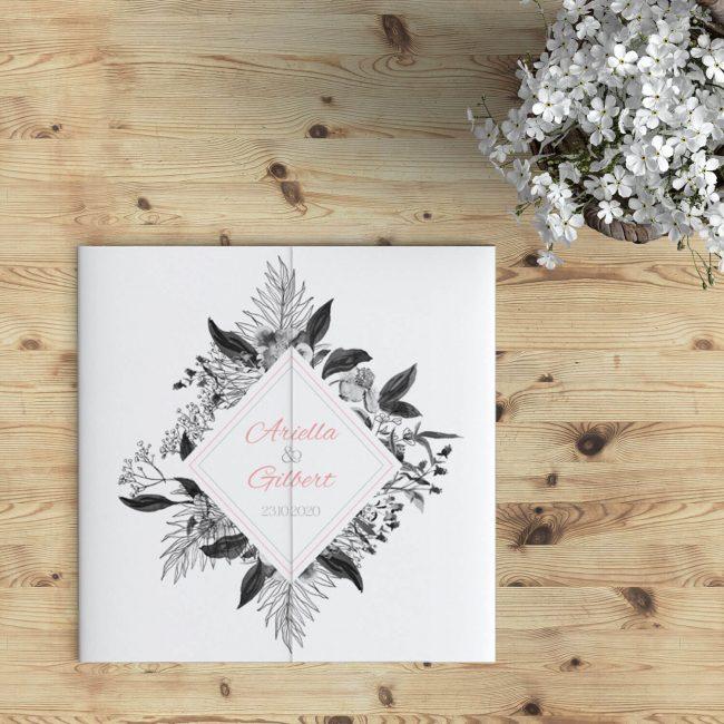 Trouwkaart Zwart Wit Bloemenspel: in het midden een frame in ruitvorm met jullie namen en de trouwdatum; daaromheen mooie, getekende zwart-wit bloemen.