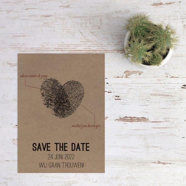 Twee vingerafdrukken die samen een hart vormen, save the date kaart Vingerafdrukken op kraftpapier presenteert de twee die samen dit hart hebben gevormd.